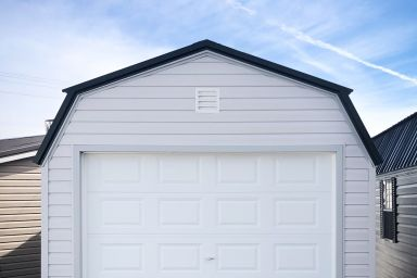 A prefab garage in Tennessee with white vinyl siding and a loft