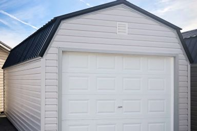 A prefab garage in Tennessee with vinyl siding and a black metal roof